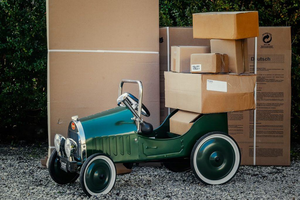 Voiture miniature entourée de cartons de déménagement