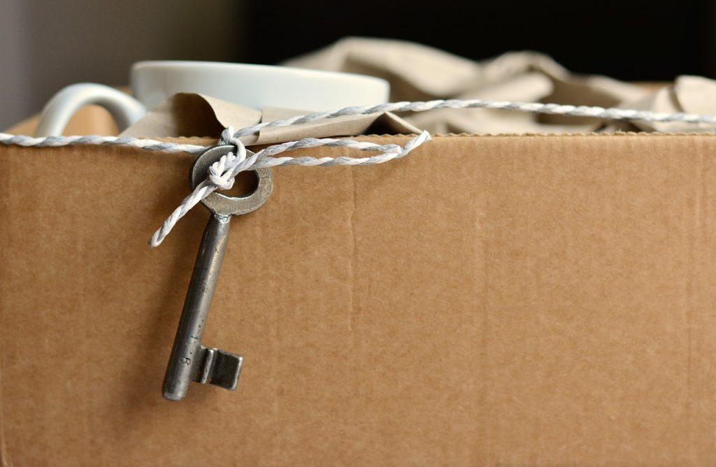 Carton de déménagement avec une tasse protégée dans du papier journal et une petite clef accrochée à de la ficelle