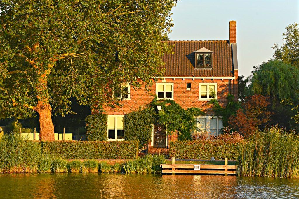 Maison sur la rive d'une rivière avec beaucoup de verdure et un ponton aménagé